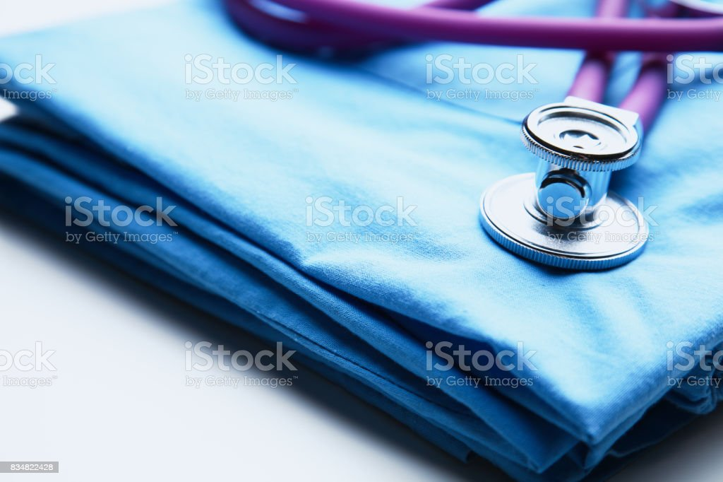 Doctor coat with medical stethoscope on the desk stock photo