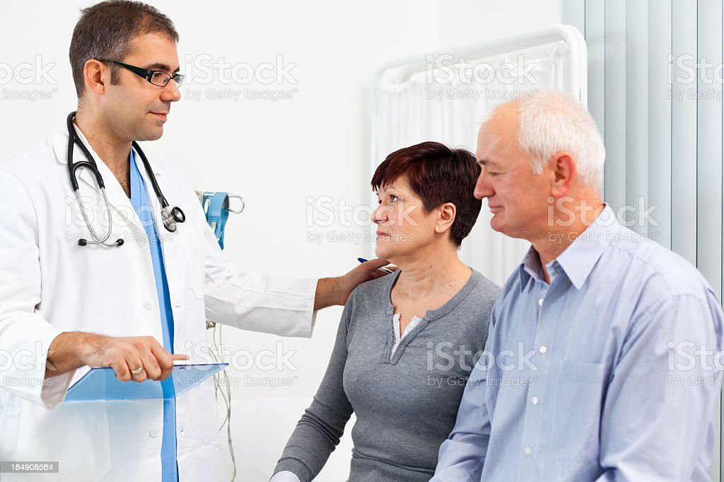 Doctor comforting mature adult patients royalty-free stock photo