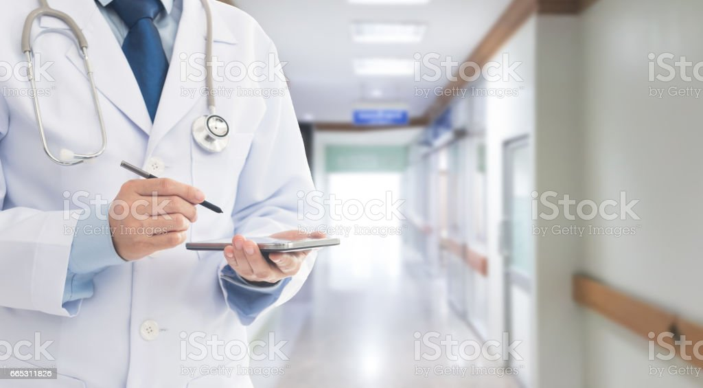 Doctor using a smart phone in hospital. Concept of healthcare and...