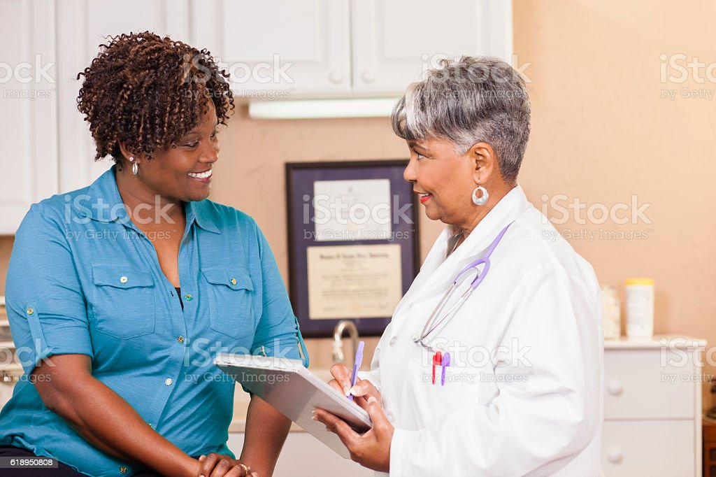 Doctor conducts medical consultation with adult patient at clinic. stock photo