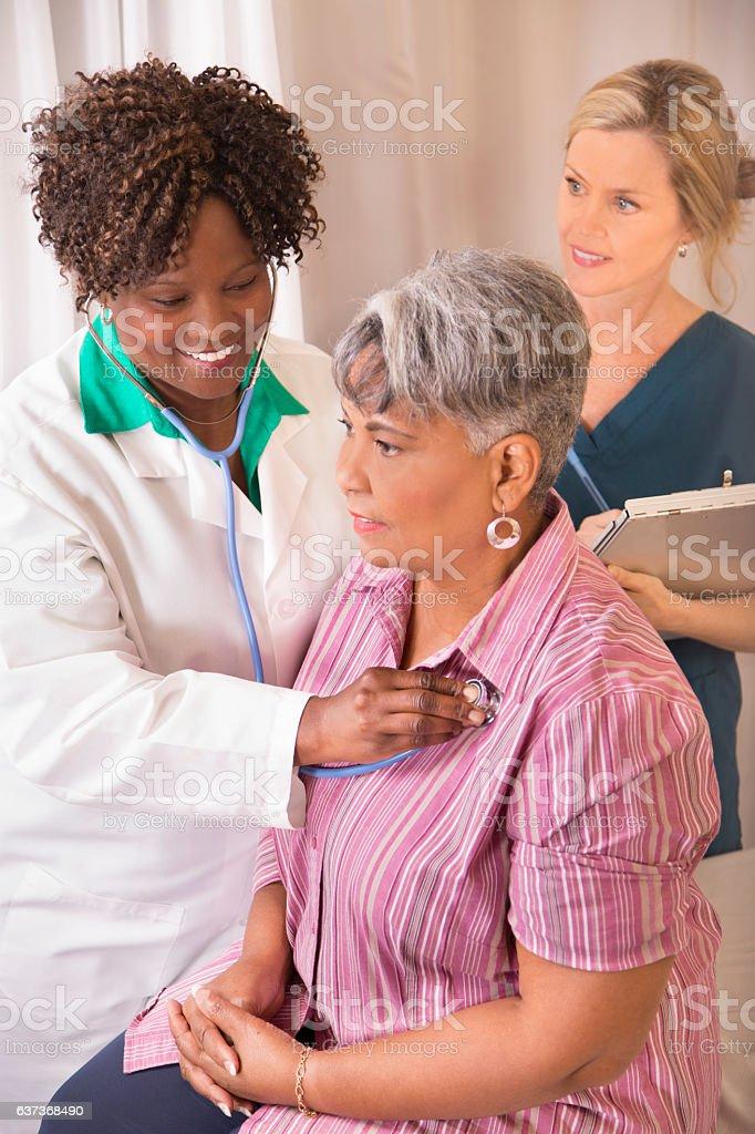 African descent, female doctor provides medical exam for senior adult...