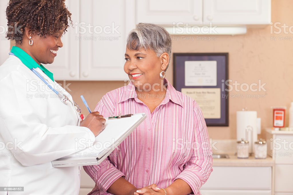 Doctor conducts medical exam with senior adult patient at clinic. stock photo