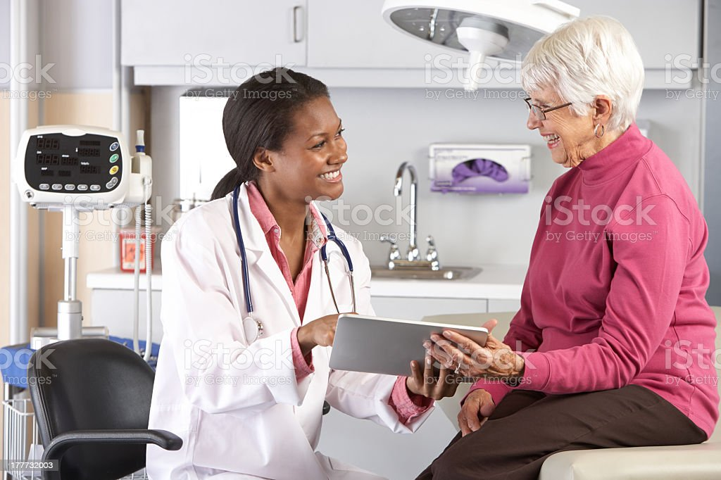 A doctor confronts a smiling senior with good news stock photo