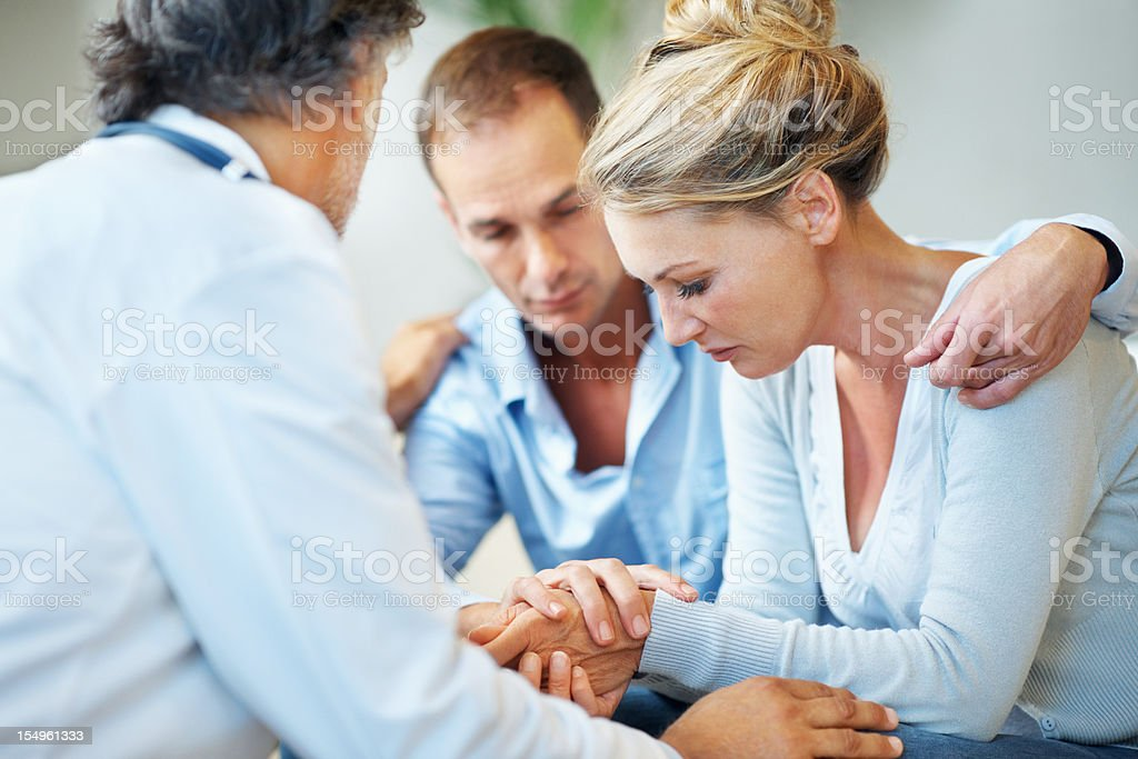 Doctor consoling a couple while giving them bad news royalty-free stock photo