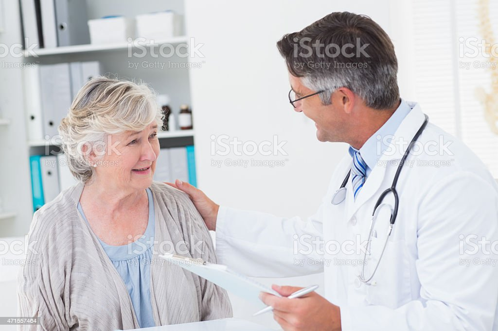 Doctor consoling senior woman in clinic stock photo