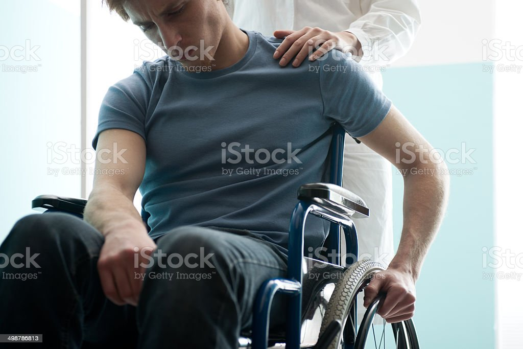 Doctor consoling young man sitting in wheelchair stock photo