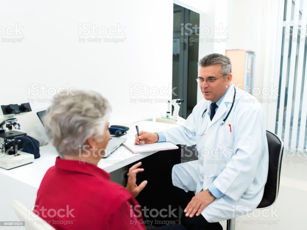 Doctor consulting female patient stock photo