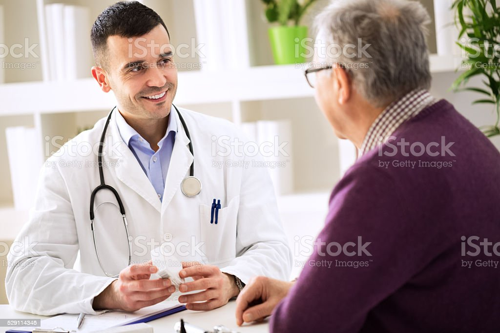 Doctor consulting patient with medicine drugs stock photo