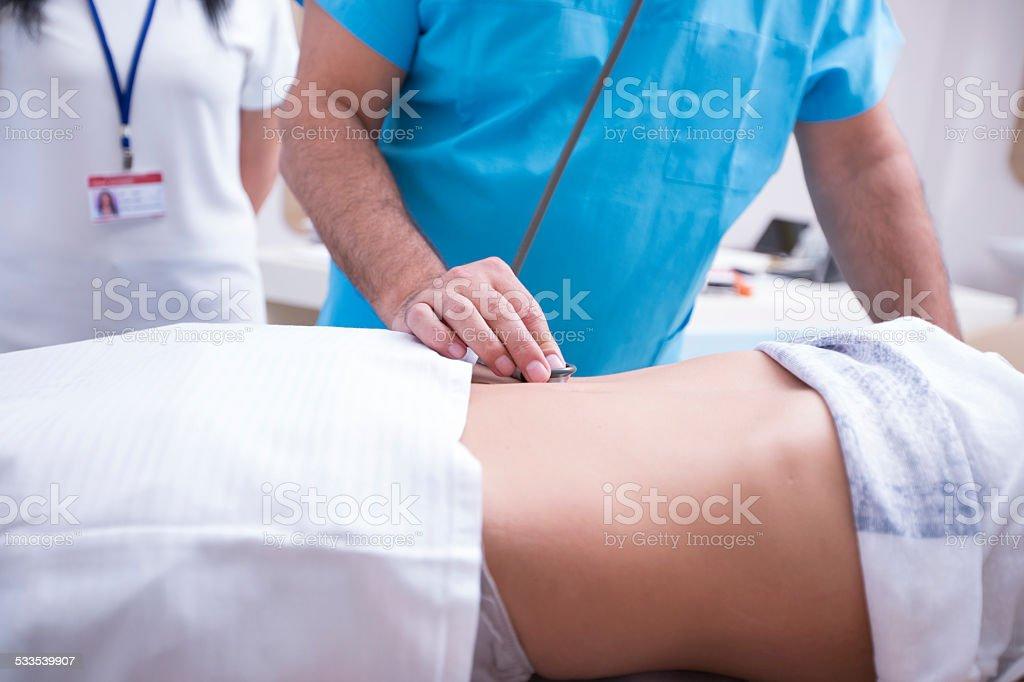 Doctor Controlling Patient In Examination Room stock photo