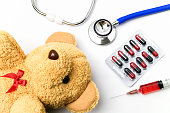 Doctor desk with medical equipment and brown teddy bear.