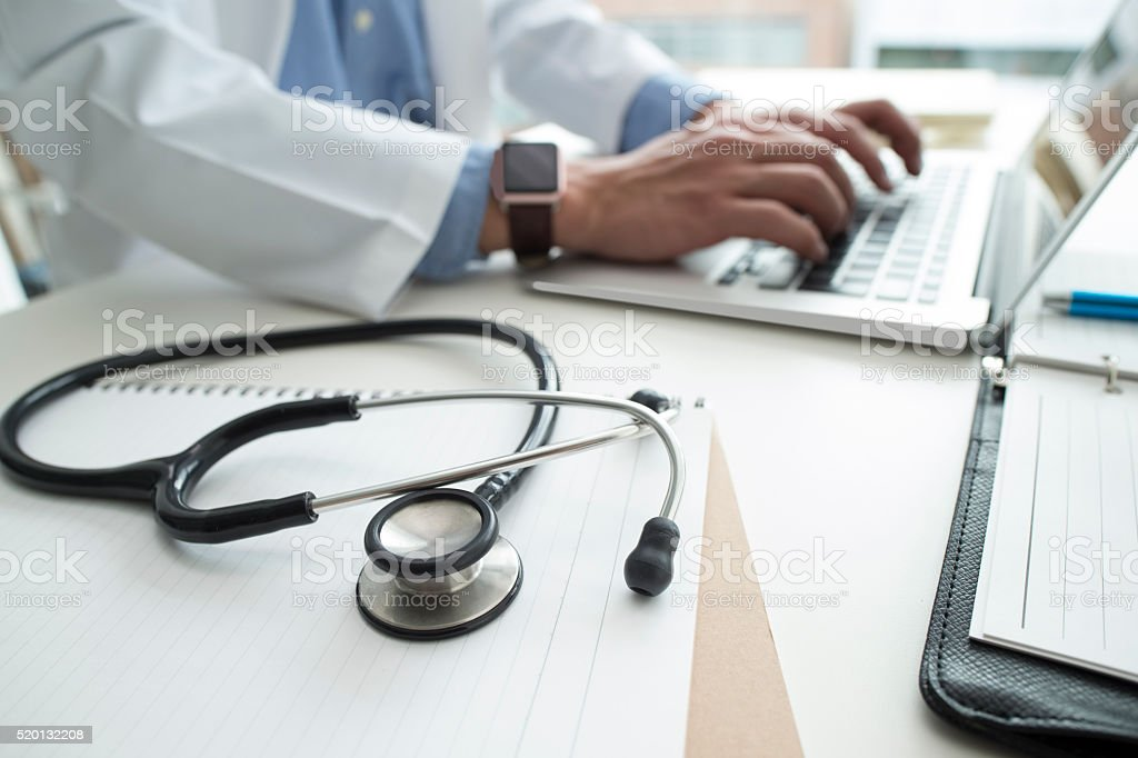 Doctor devoted the data to a laptop stock photo