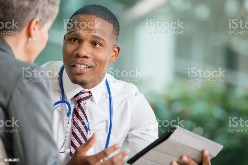 Doctor discussing hospital policy changes with senior patient in office stock photo