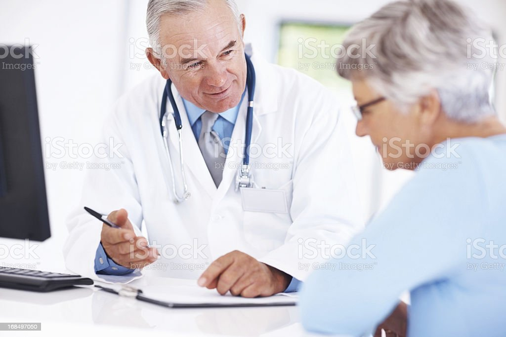 Doctor discussing medical report with senior patient royalty-free stock photo