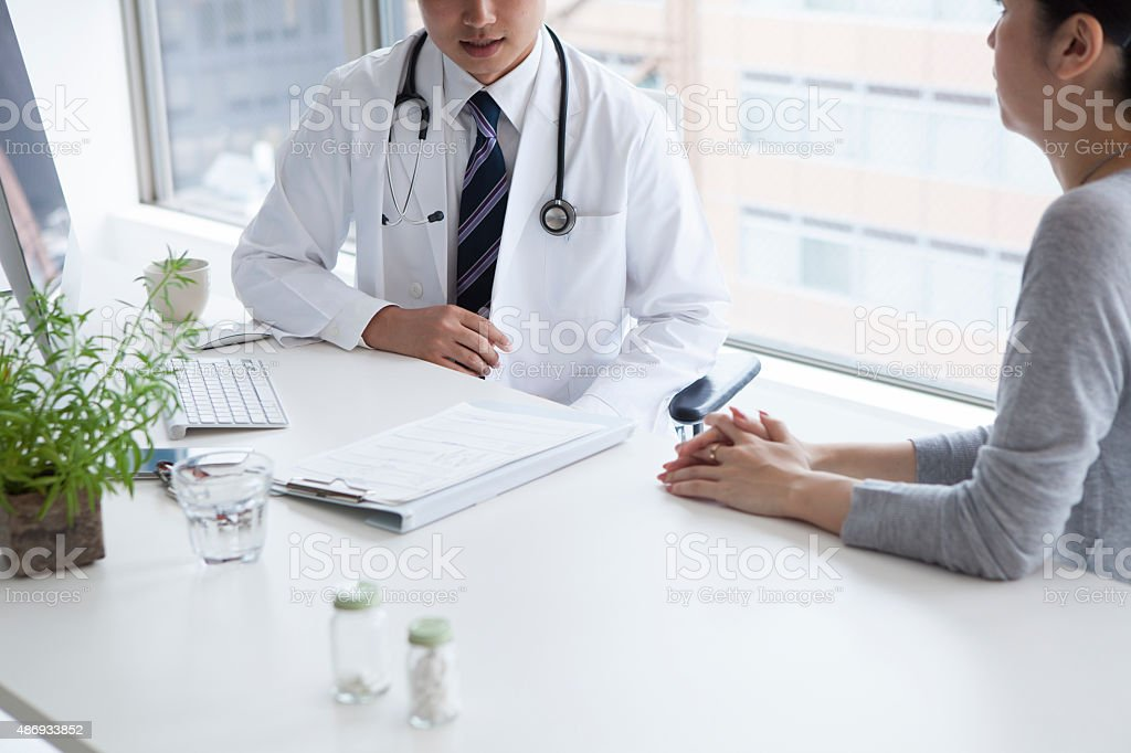 Doctor discussing with female patient in clinic stock photo