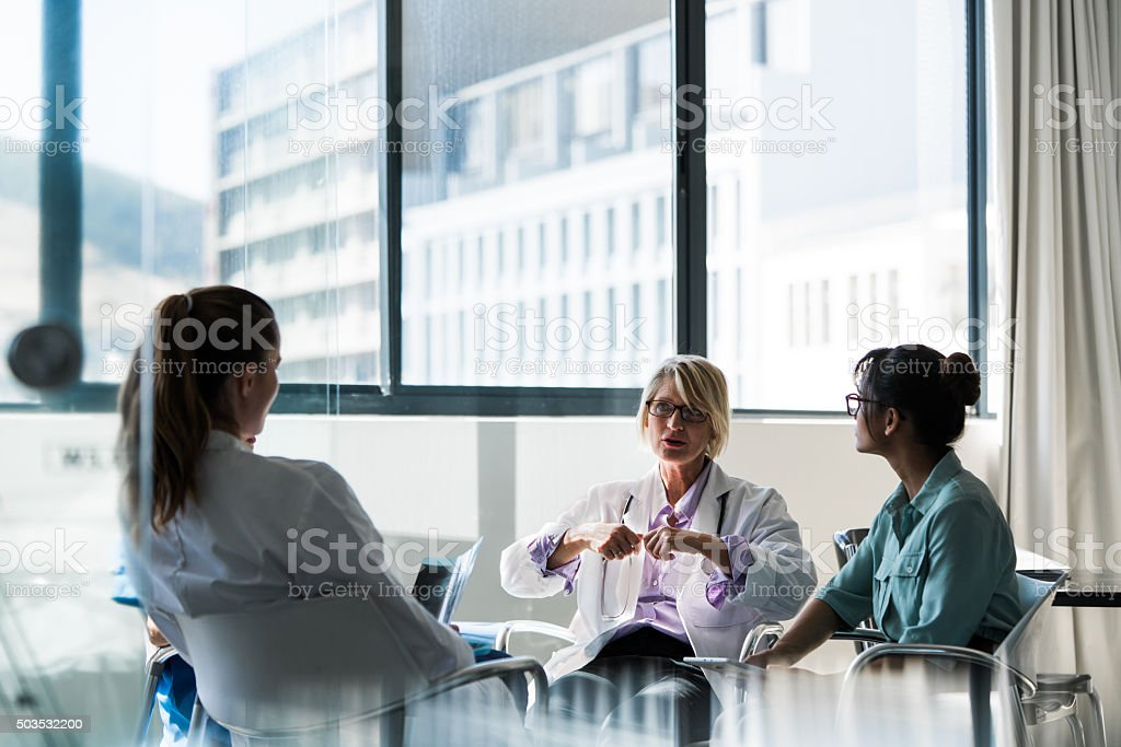 Doctor discussing with team in hospital stock photo