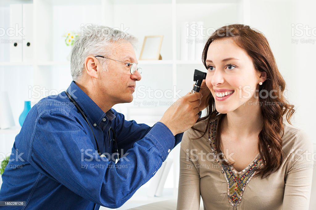 Doctor Doing Ear Exam With Otoscope stock photo
