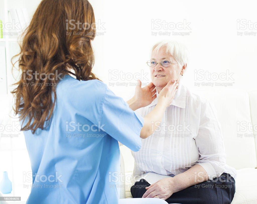 Doctor Doing Glands Exam to Senior Woman. stock photo