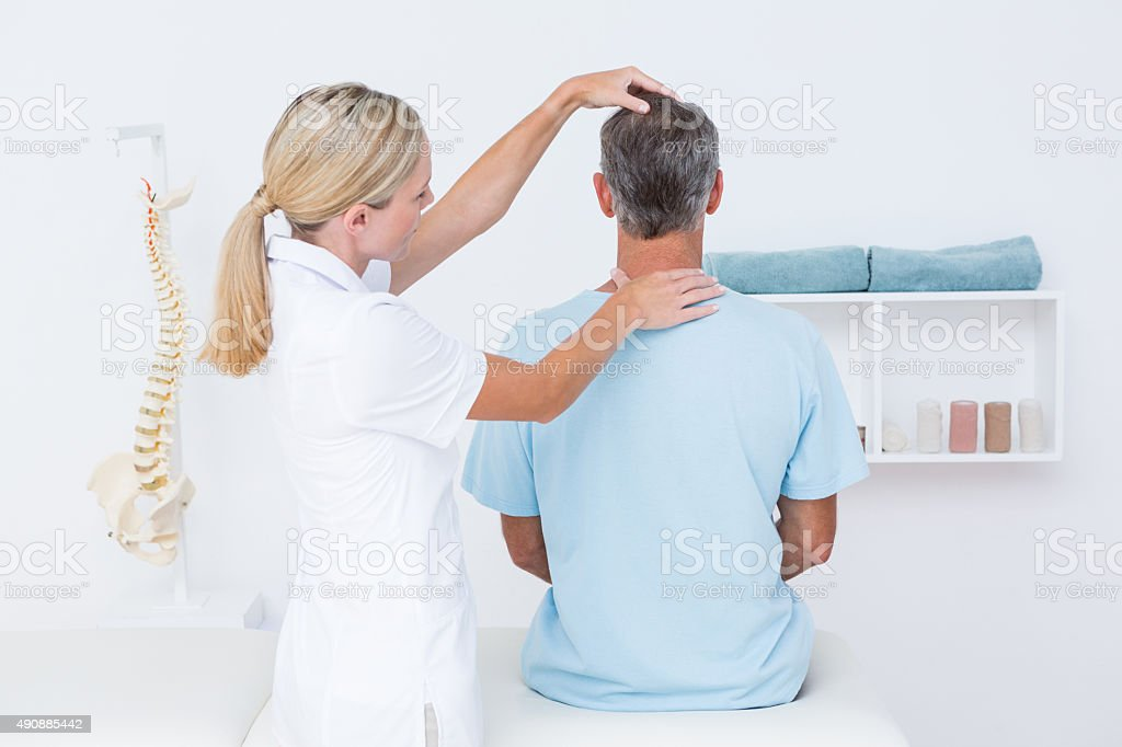 Doctor doing neck adjustment stock photo