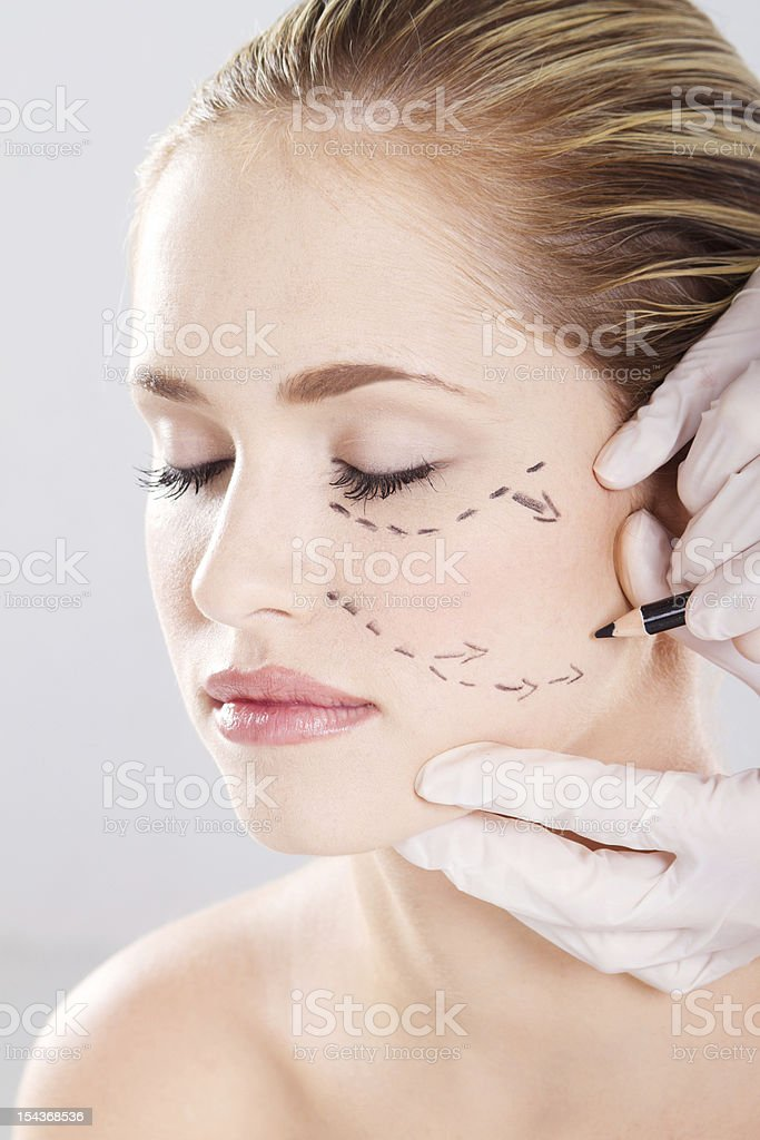 doctor draw correction lines on woman face stock photo