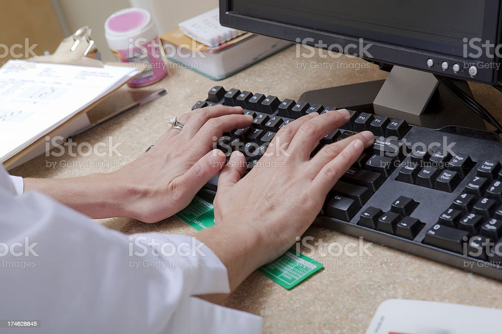 Doctor Enters Data into Computer royalty-free stock photo