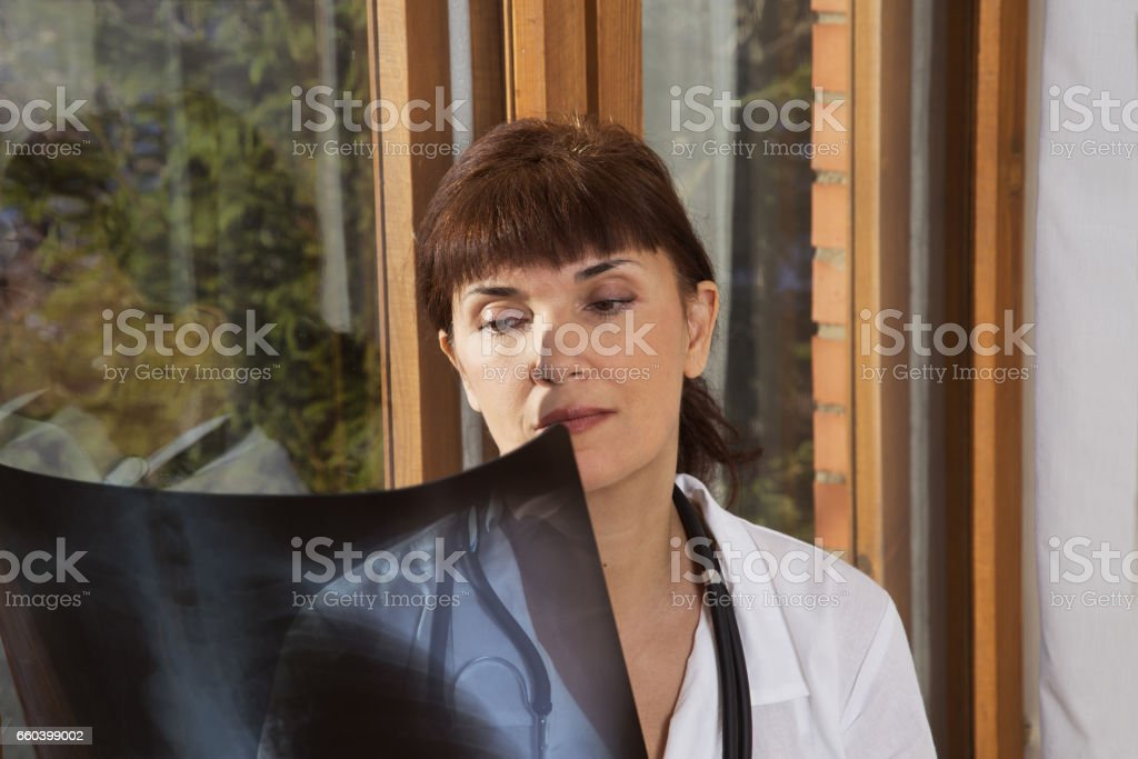 doctor examines a radiograph near a window stock photo