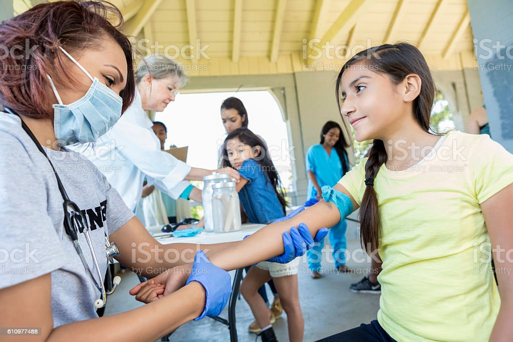 Doctor examines preteen patient at free clinic stock photo
