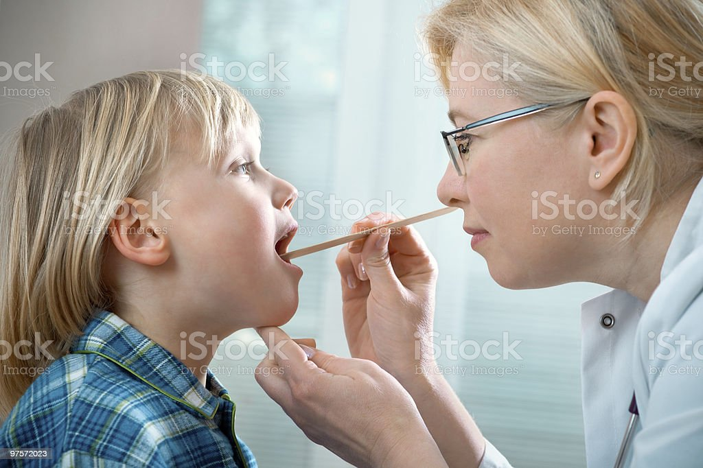 Doctor examining a child's throat with a tongue depressor stock photo