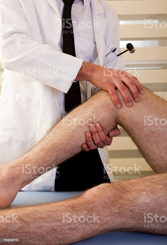 Doctor examining a man's leg and knee stock photo