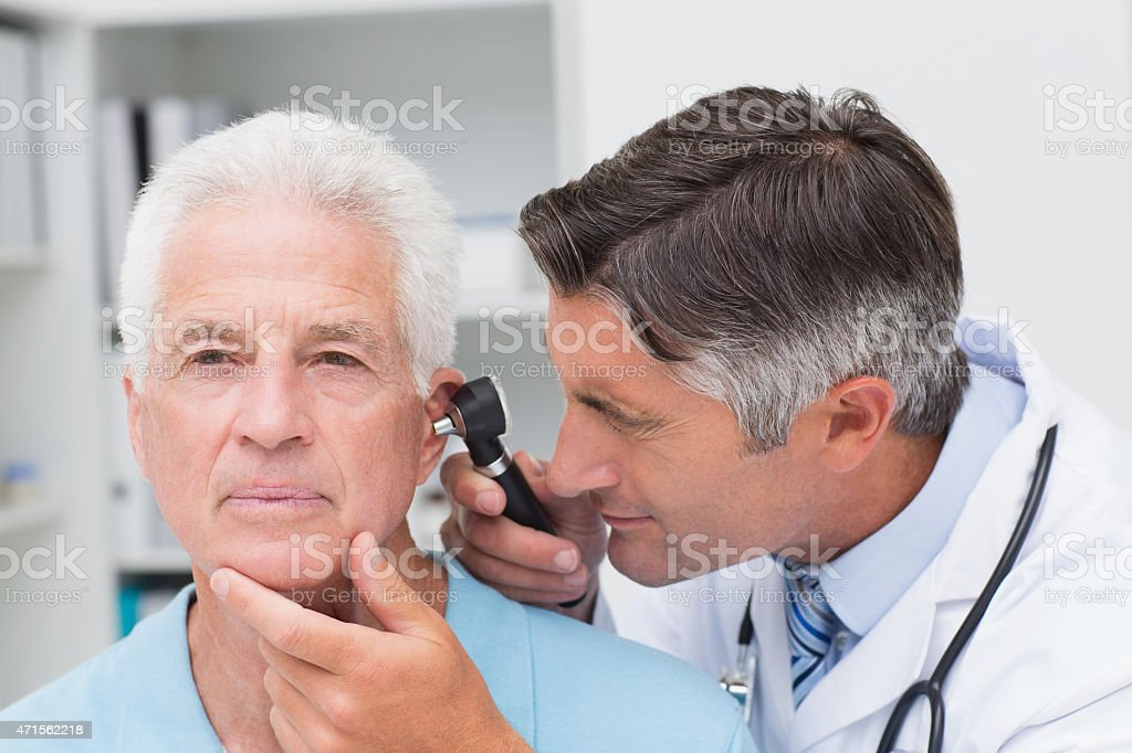 Doctor examining an elderly patient's ear with an otoscope stock photo