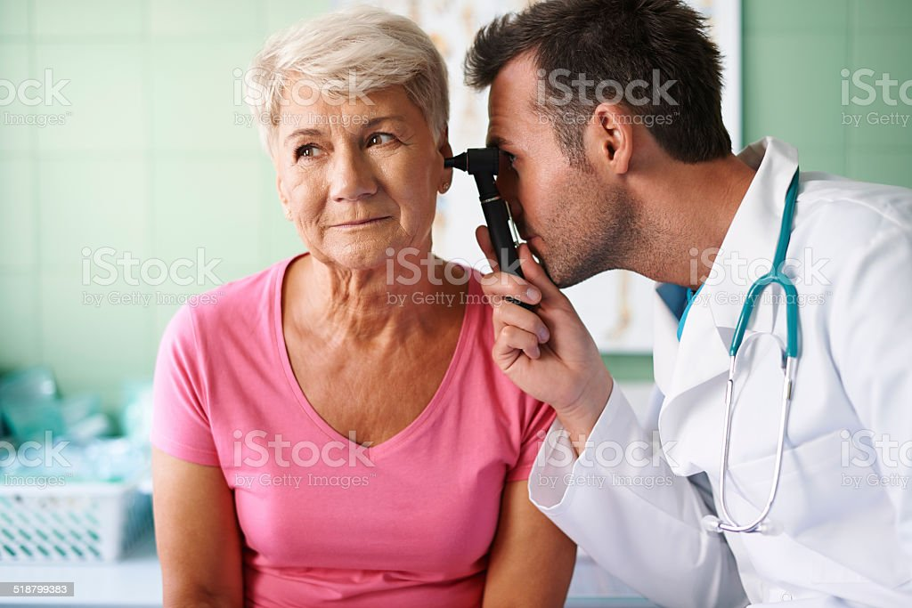 Doctor examining ear of senior woman stock photo