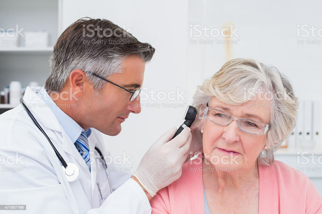 Doctor examining female patients ear with otoscope stock photo
