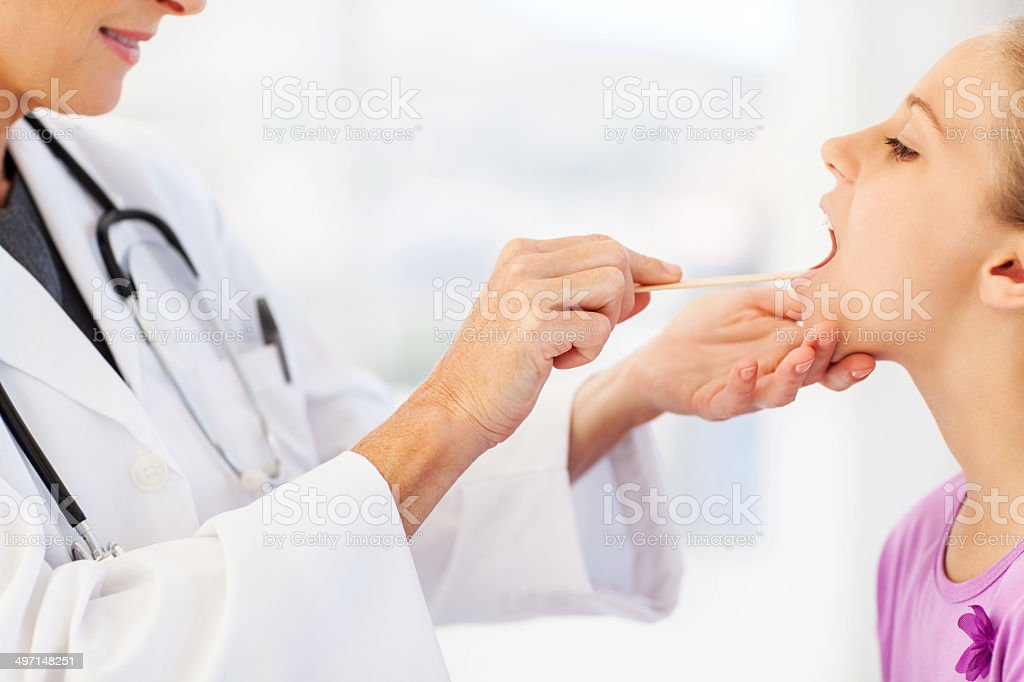 Doctor Examining Girl's Throat In Clinic stock photo