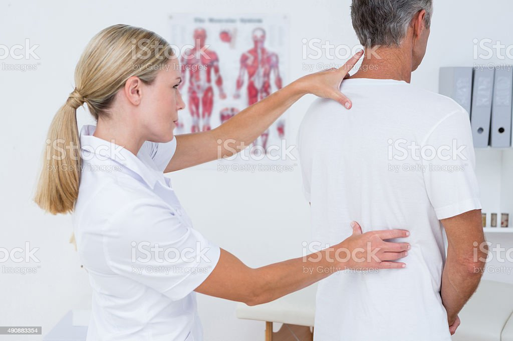 Doctor examining her patient back stock photo