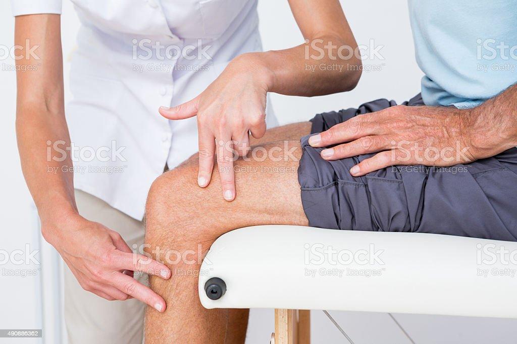 Doctor examining her patient knee stock photo