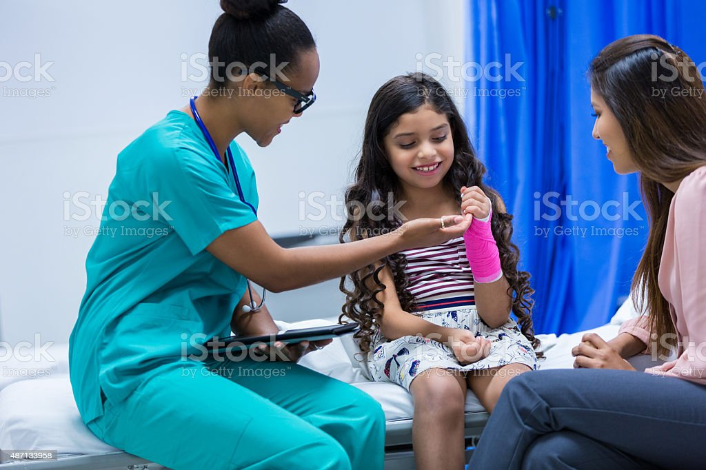 Doctor examining little girl's injured arm in emergency room stock photo