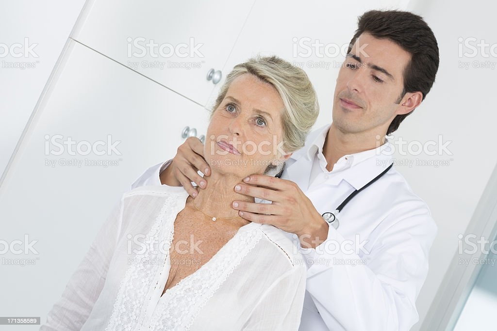 doctor examining lymph node of senior patient stock photo