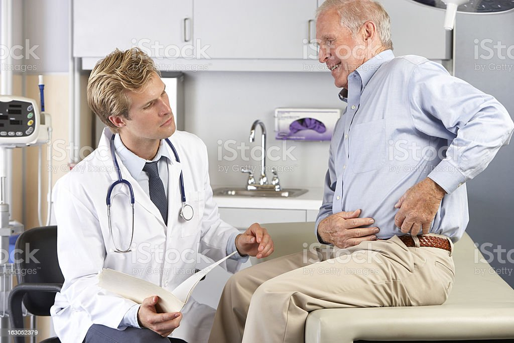 Doctor Examining Male Patient With Hip Pain stock photo