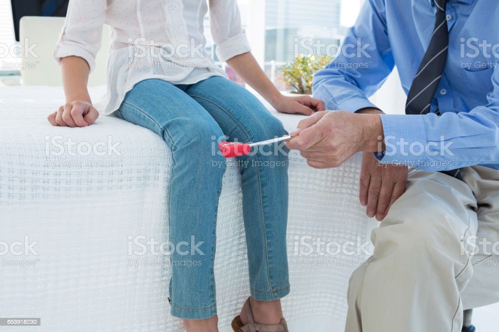 Doctor examining patient knee by using test hammer stock photo