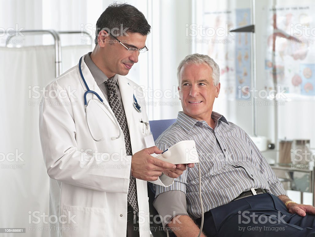 Doctor examining patient's blood pressure, at hospital royalty-free stock photo