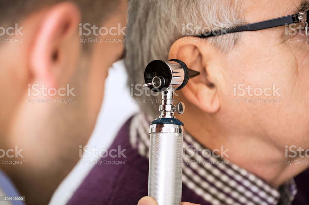 Doctor Examining Patient's Ear stock photo