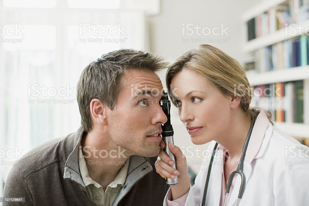 Doctor examining patients eye in doctors office royalty-free stock photo