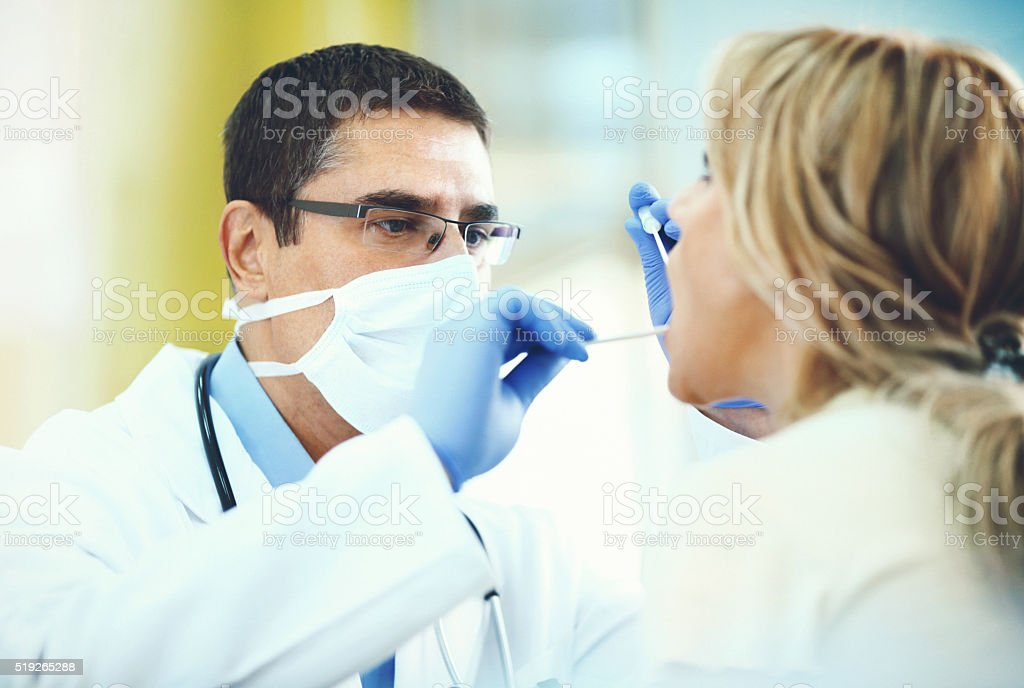 Doctor examining patient's throat. stock photo