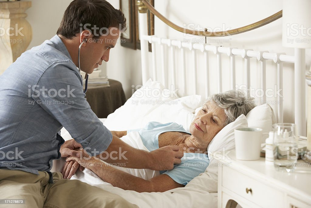 Doctor Examining Senior Female Patient In Bed At Home stock photo