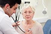 Doctor Examining Senior Female Patient In Hospital