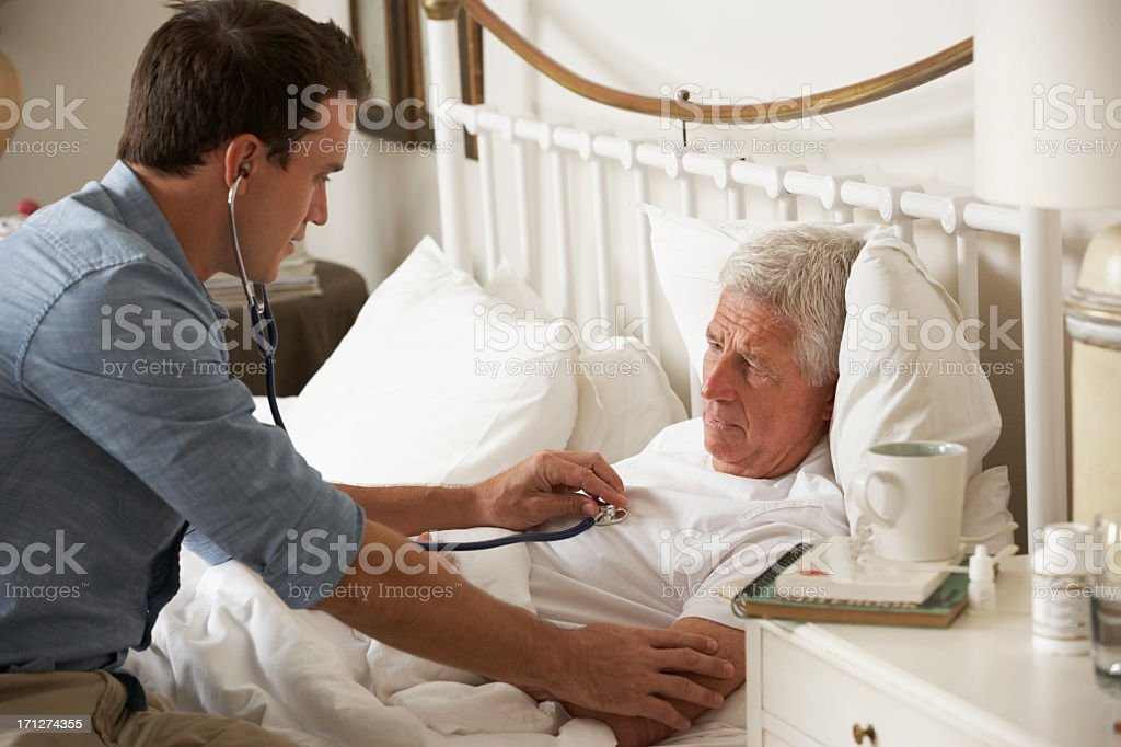 Doctor Examining Senior Male Patient In Bed At Home stock photo