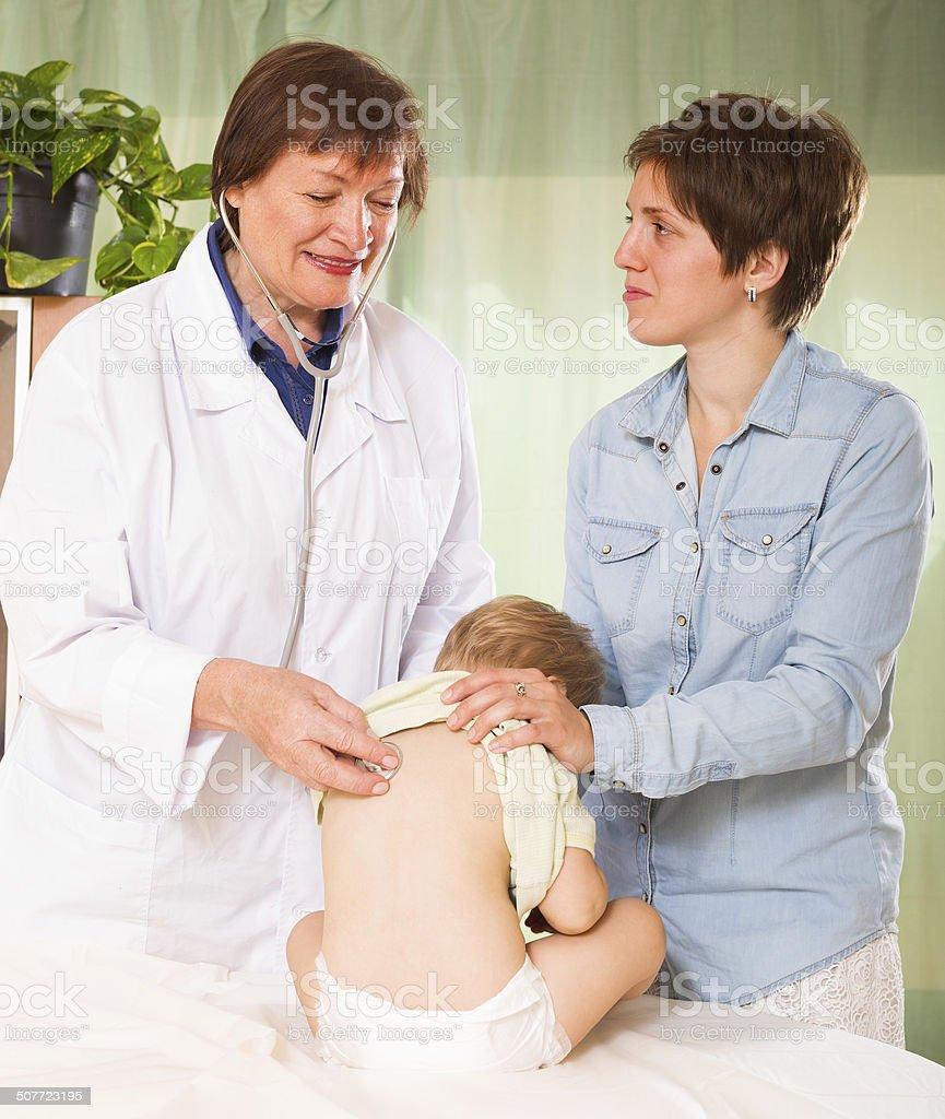Doctor examining toddler stock photo