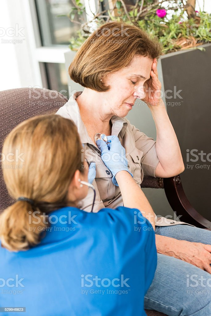 Doctor examining with stethoscope the lung of senior patient, stock photo