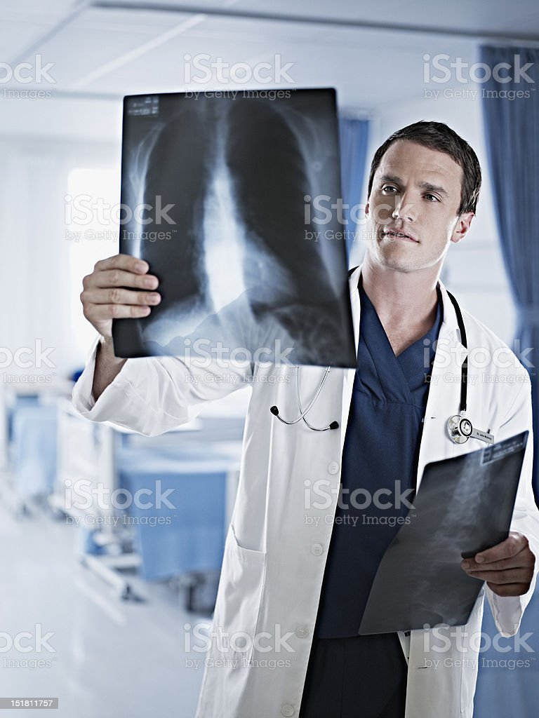 Doctor examining x-rays in hospital room royalty-free stock photo