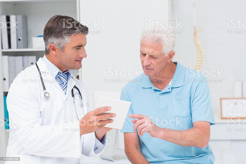 A doctor explaining a prescription to a senior patient stock photo