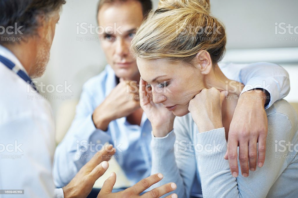 Doctor explaining medical details to a couple stock photo